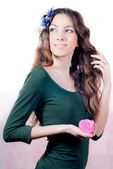 Young beautiful woman with flowers in hair and hands — Stock Photo