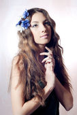 Young beautiful woman with flowers in hair — Stock Photo