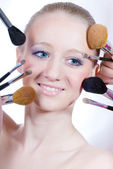 Young woman with makeup brushes — Stock Photo