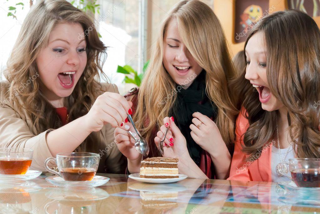 Молодые девушки едят торт стоковое