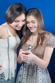 Two smiling girls with cell phone — Stock Photo