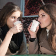 Two beautiful young girls drinking coffee — Stock Photo