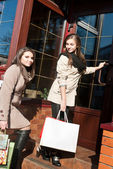 Two young women by shop entrance — Stock Photo