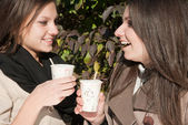 Two beautiful young girls drinking coffee — Stok fotoğraf