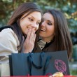 Two beautiful young girls sharing secrets — Stock Photo