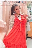 Beautiful young girl choosing a dress — Стоковое фото