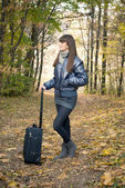 Beautiful young girl with a suitcase in the forest — Stockfoto