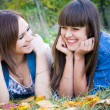 Two girls lying in autumn leaves — Stock Photo #10432704