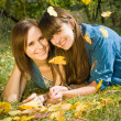 Two girls lying in autumn leaves — Stock Photo