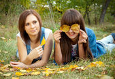 Two girls joking with yellow leaves — Stock Photo