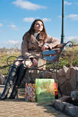 Woman with shopping bags sitting on bench — Stock Photo