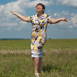 Happy mature woman standing in the field under blue sky — Stock Photo