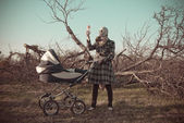 Mother in gas mask with baby buggy — Stock Photo