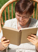Mature woman reading book and laughing in rocking chair — Stock Photo
