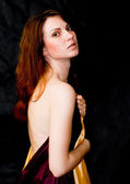 Woman holding satin fabrics with naked shoulder — Stock Photo