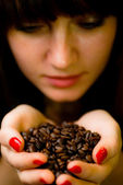 Young woman with coffee beans — Stock Photo