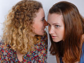 Two girl friends sharing a secret — Stock Photo