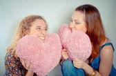 Duas meninas rindo e segurando corações — Foto Stock