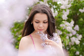 Young pretty woman smelling pink lilac — Stock Photo
