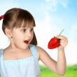 Funny surprised child girl with strawberry — Stock Photo