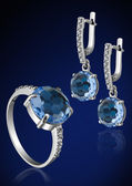 Jewelry set with brilliants on blue — Stock Photo