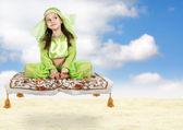 Little arabian girl sitting on flying carpet — Stock Photo