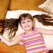 Happy child girl resting on soft pillow — Stock Photo