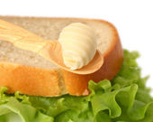 Butter curl on wooden spoon with bread — Stock Photo