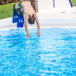 Boy  jumping in the blue pool - Foto de Stock