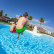 Stock Photo: Boy jumping in the blue pool