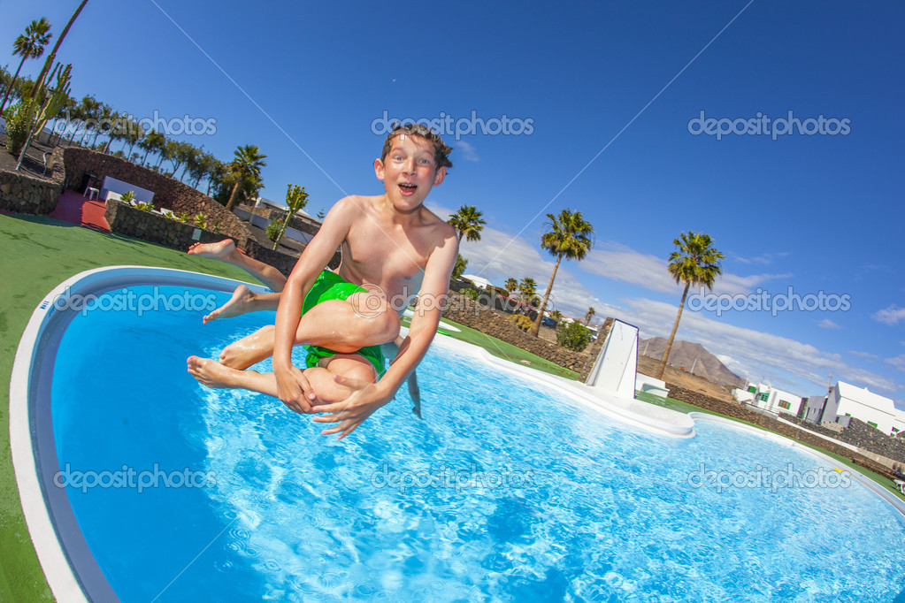 Boy has fun jumping in the pool  Stock Photo #10105797