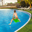 Boy  jumping in the blue pool - Stock Photo