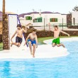 Three boys jumping in the pool - Stock Photo