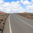 Road through lava rocks and volcanic mountains. Los Hervideros. - Stock Photo