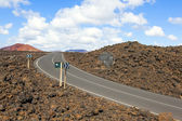 Road through lava rocks and volcanic mountains. Los Hervideros. — Stock Photo