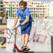 Boy rides his scooter at the skate park — Stock Photo