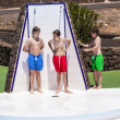 Boys have fun unter the pool shower - Stock Photo