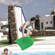 Stock Photo: Boy jumping in the pool with the surfboard