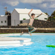 Boy jumping in the pool with the surfboard — Stock Photo
