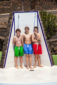 Boys have fun unter the pool shower — Stock Photo