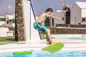 Pojken hoppar i poolen med surfbräda — Stockfoto