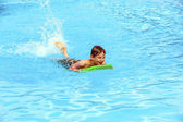 Boy paddling on the surf board — Stock Photo