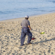 Government man cleans the beach - Stock Photo