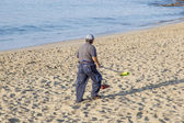 Government man cleans the beach — Stock Photo