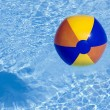 Inflated plastic ball flying in pool — Stock Photo #10448512