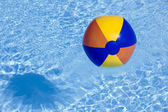 Inflated plastic ball flying in the pool — Stock Photo