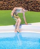 Boy testing the temperature of the pool water — Stock Photo