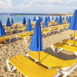 Stock Photo: Umbrellas and empty beach couches at beach in morning light