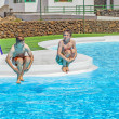 Two  friends jumping in the pool — Stock Photo