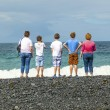 Family watches the waves at the  black volcanic beach — Stock Photo